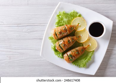 Grilled squid on a plate with lemon and sauce. horizontal view from above