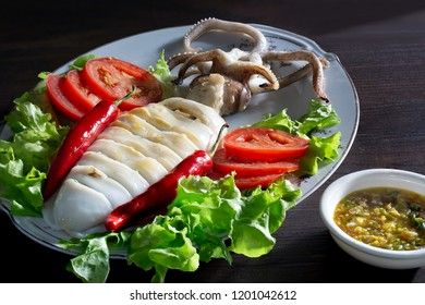 Grilled squid  with vegetable in white dish and seafood sauce on dark table / Select focus and space for texts