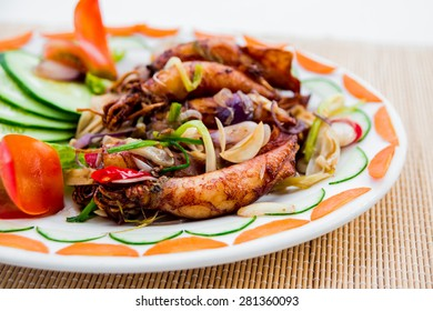 Grilled squid with vegetables on a white plate. Restaurant