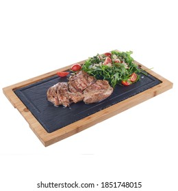 Grilled stake with rocket salad and tomatoes made in gourmet style on fancy plate isolated on white background