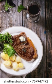 Grilled steak with butter, potatoes and green salad on white ceramic plate and vintage glass with red wine over old wooden table. Top view. See series