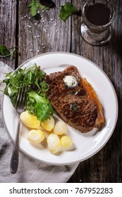 Grilled steak with butter, potatoes and green salad on white ceramic plate and vintage glass with red wine over old wooden table. See series