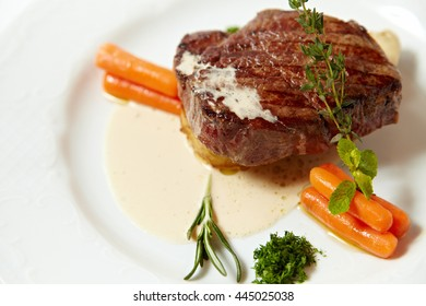 Grilled steak with carrots, close up isolated on white