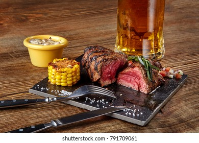 Grilled steak with corn with mushrooms sauce on cutting board and mug of beer on wooden table
