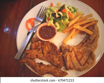 Grilled steak with french fries and vegetables on plate