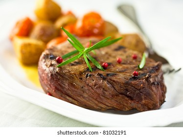 Grilled steak with fresh rosemary and peppercorns served with grilled vegetables. Concept for a tasty and healthy meal. Close up