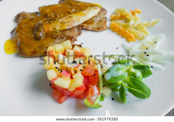 grilled steak and fried fish fillet with vegetables on the table in shop.