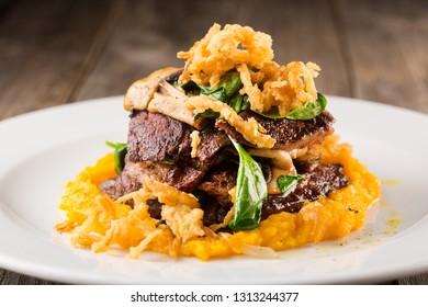 Grilled steak with mashed vegetables