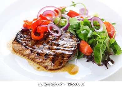 Grilled steak meat with salad from baked pepper on white plate.