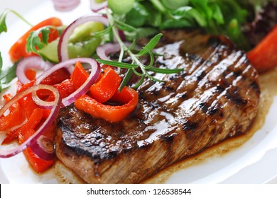 Grilled steak meat with salad from baked pepper