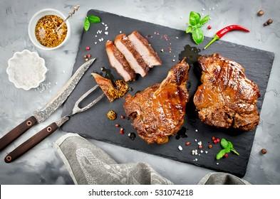 Grilled Steak on bone with knife and fork carving set on black stone slate. Sliced grilled Steak on bone pork rib