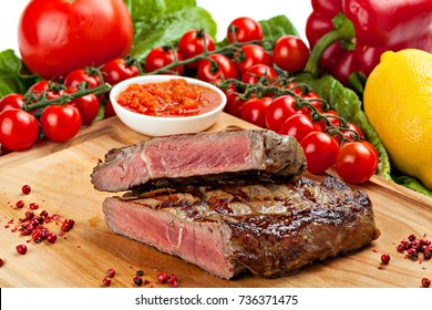 Grilled steak on a cutting board with vegetables.