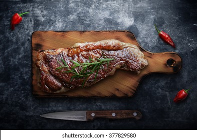 Grilled steak with peppers on blackboard background