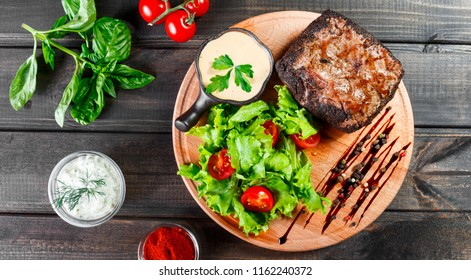 Grilled steak pork with fresh vegetable salad, tomatoes and sauce on wooden cutting board
