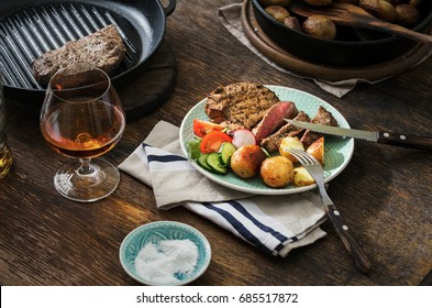 Grilled steak with potatoes and salad in a plate on a wooden table with glass of whiskey. Dinner table concept