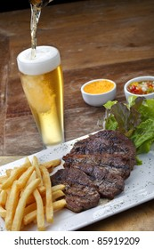 Grilled Steak with salad and beer