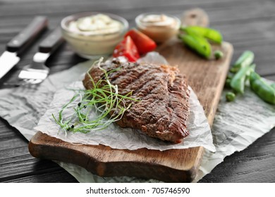 Grilled steak with sauces and vegetables on cutting board