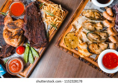 Grilled steak served with vegetables and herbs decorated with napkin over rustic wooden board