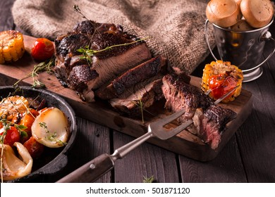 Grilled Steak sliced on a cutting board. Meat with Grilled Vegetables. Wooden background.