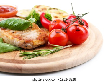 Grilled steak with spices, herbs and vegetables  on wooden board, isolated on white