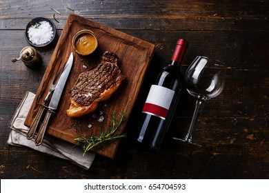 Grilled Steak Striploin with Peppercorn sauce and bottle of Red wine on wooden background