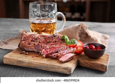 Grilled steak with tomatoes on cutting board and mug of beer on wooden table