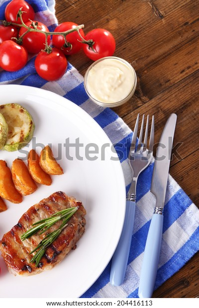 Grilled steak, grilled vegetables and fried potato pieces on table background
