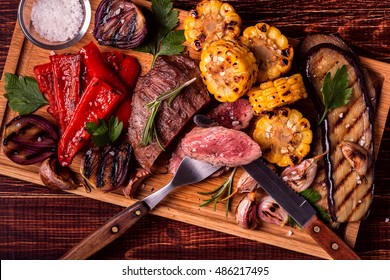 Grilled steak and vegetables on cutting board, top view.