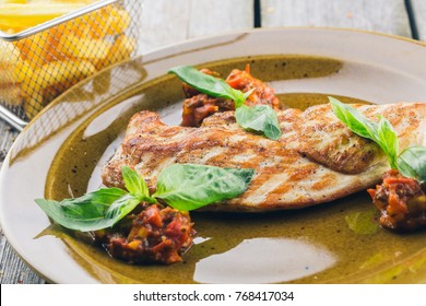 Grilled steaks and fries potatoes on wooden background close-up