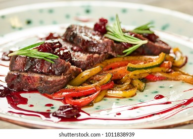 Grilled steaks and vegetables. Grilled steaks, vegetables, rosemary and cherry sauce.