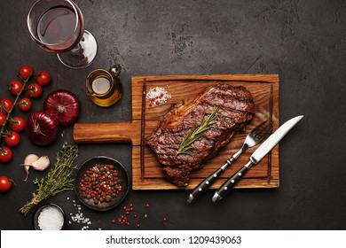 Grilled Striploin beef steak on wooden board with glass of wine, vegetables, herbs and spices on dark stone background. Top view