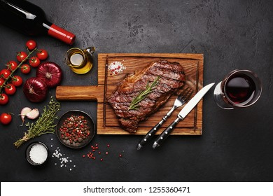 Grilled Striploin beef steak on wooden board with bottle and glass of red wine, vegetables, herbs and spices on black stone background. Top view
