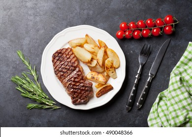 Grilled striploin steak with roasted potato on plate over stone table. Top view