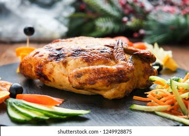 Grilled stuffed chicken fillets with vegetables on a slate shale plate
