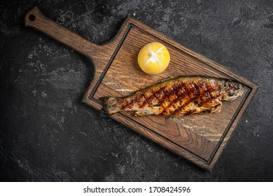 Grilled sturgeon, carp, crucian or trout with grilled vegetables on the board. Beautiful stylish menu. Autumn still life. Free space for text