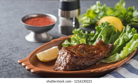 Grilled sturgeon on a plate with lemon and sauce. Grilled sturgeon on a plate with copyspace