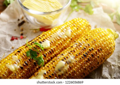 Grilled sweet corn cob with melting butter and greens on baking paper