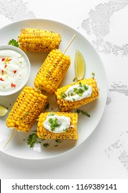 Grilled sweet corn with white mexican sauce, chilli and lime. healthy summer food