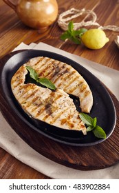 grilled swordfish slices in a cast iron pan on a wooden table, garnished with mint, oregano, salt and salmoriglio