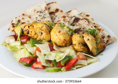 Grilled tandoori chicken with chapati and salad on white plate