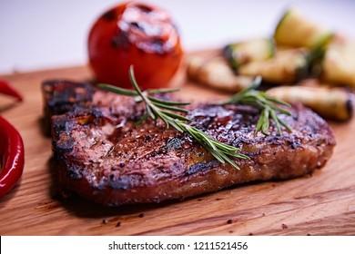 Grilled T-Bone Steak on serving board on wooden background