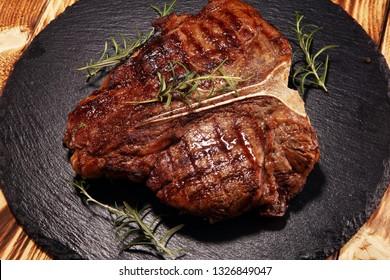 Grilled T-bone steak on stone plate. bbq grill bone steak set