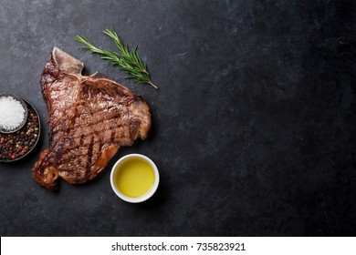 Grilled T-bone steak on stone table. Top view with copy space