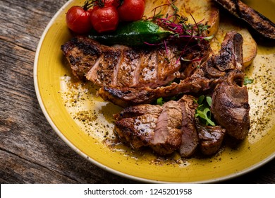 Grilled T-bone steak seasoned with spices and fresh herbs served on a wooden board with fresh tomato and roast potatoes