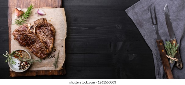 Grilled T-Bone steak with spices, knife and fork.Fla lay