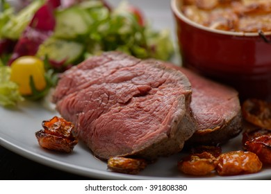 Grilled tenderloin with potatoes in the background
