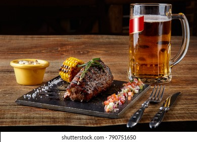 Grilled tenderloin Steak roastbeef and mushrooms sauce on black cutting board and glass of beer on wooden table