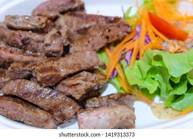 Grilled tenderloin.Barbecue.Meat cut into pieces.Beef steak.Sprinkle with black pepper.