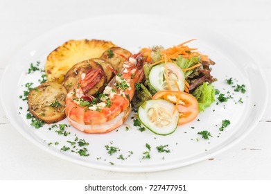 Grilled tiger prawn with potatoes, tomatoes and salad on the white plate