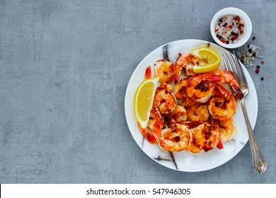 Grilled tiger prawns in white plate with lemon and spices on vintage grey background, top view, copy space. Stone kitchen table with seafood dinner. Slow food concept